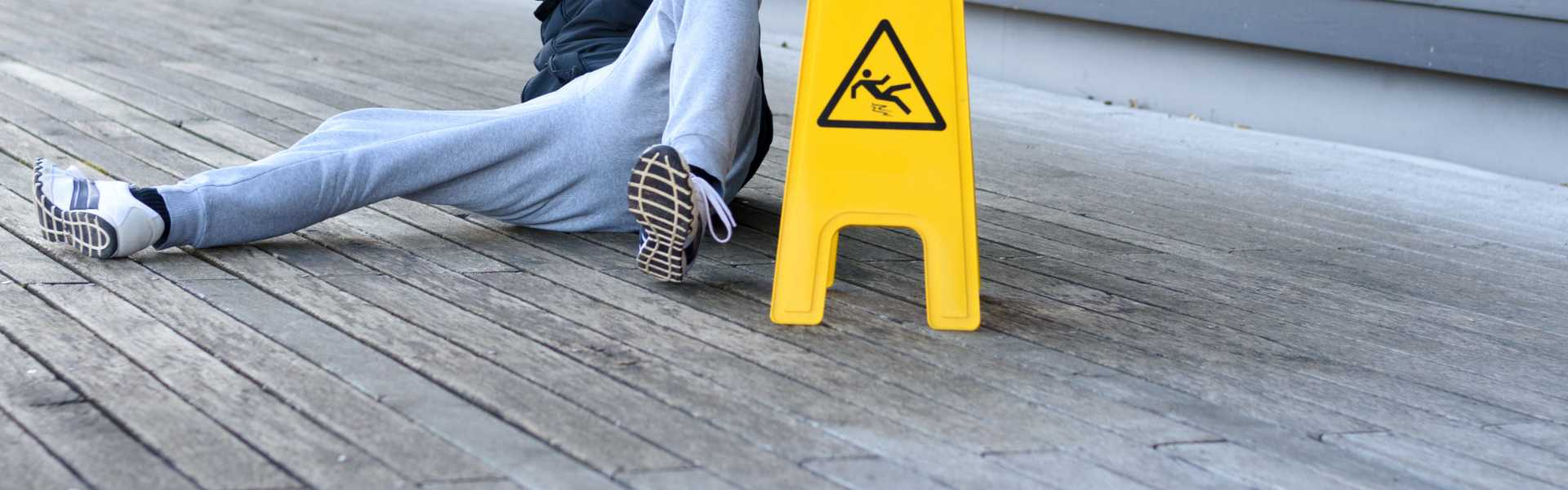 A person on the ground near a warning sign after a slip and fall accident