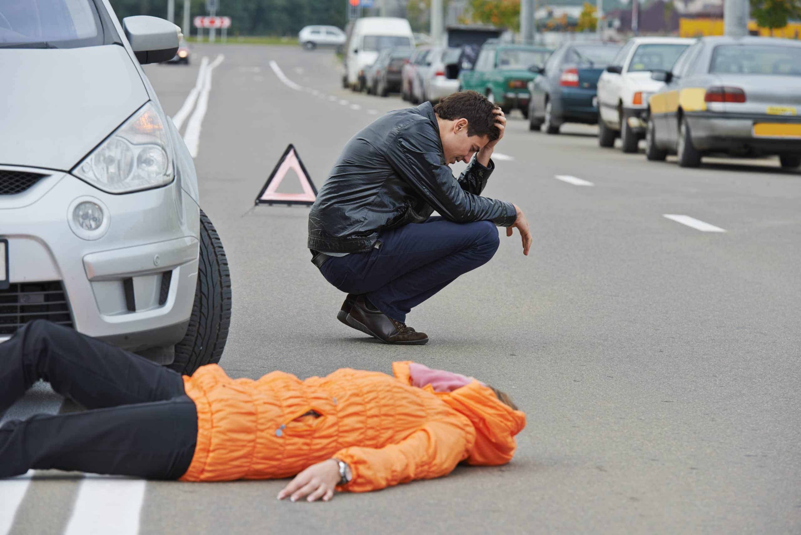 An upset driver kneels near an injured person on the roadway after a car accident