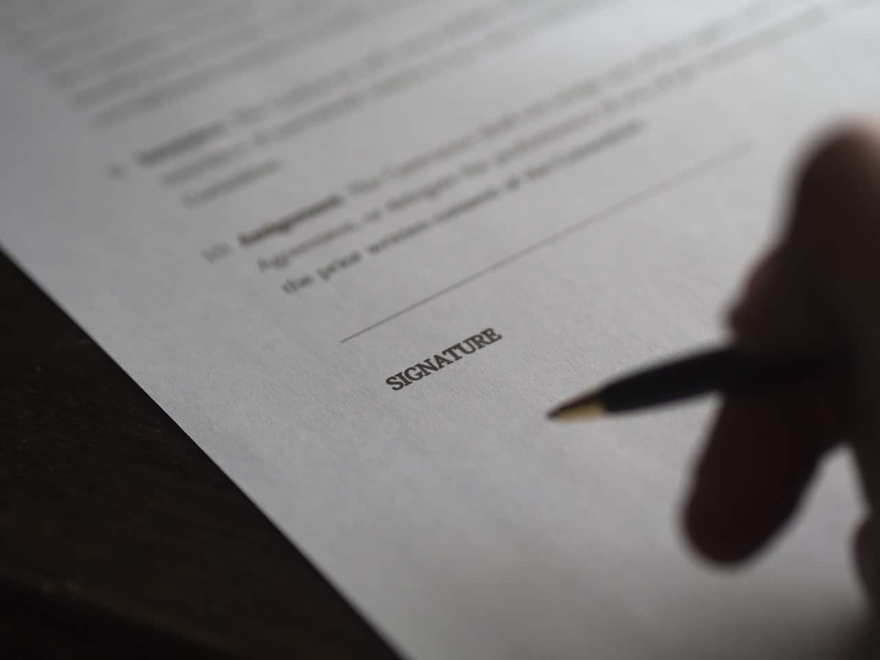 Hand signing a contract with a personal injury lawyer after an accident